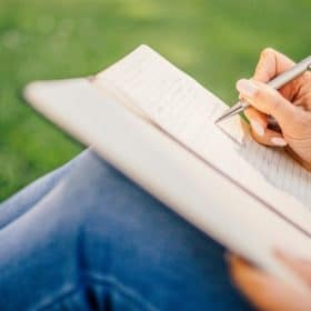 female online homeschool student writing in notebook for the Adult Write Your Own Novella online course on Luma Learn