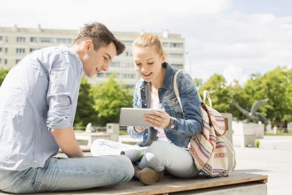 Young woman with male friend using digital tablet at college campus. online courses for high school