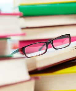 eyeglasses among piles of books used for an online course on luma learn