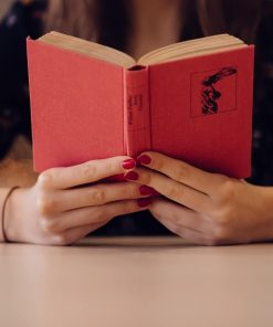 woman reading red book for online course on Luma Learn