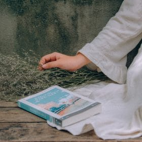 female outside with notebook studying for online course