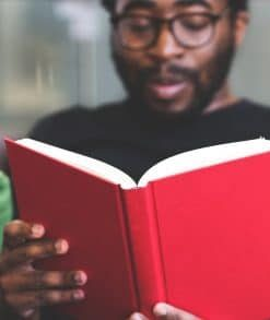 male with red book reading for online course on luma learn