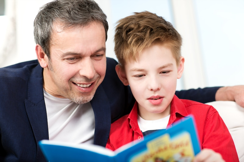 Dad and son reading a book at home